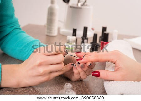 Manicurist treating client at beauty nails salon. Manicure, painting on nail - stock photo