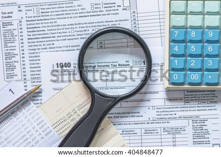 Manifier glass looking at text heading of US Income tax return empty blank paper form for American residents with blur calculator and bank book record background: USA Tax day concept