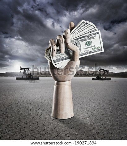 Manikin hand holding money in dry lake bed with storm clouds and drilling rigs in background - stock photo
