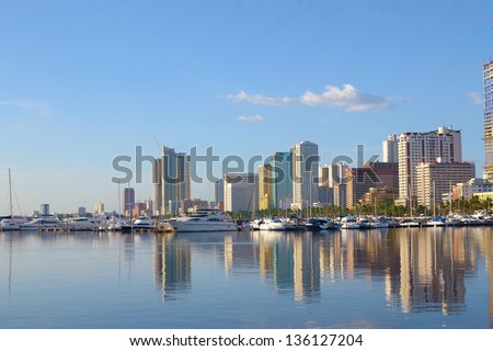 Manila bay Philippines city scape with yachts and luxury boats on summer afternoon.