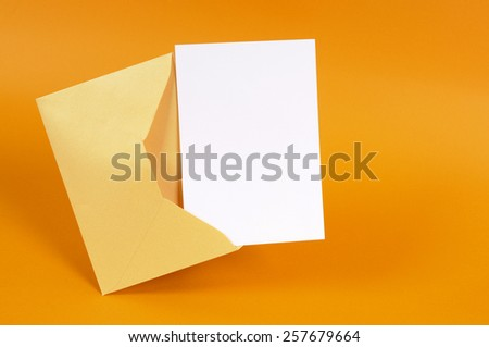 Manila envelope, blank message card, gold background. - stock photo