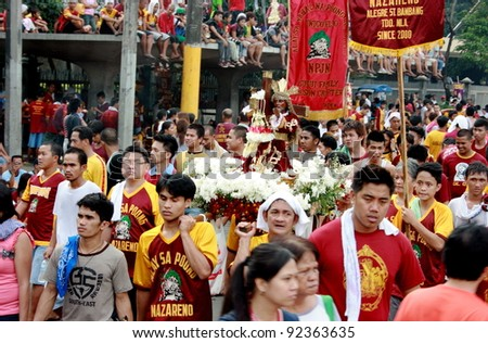 MANILA - JAN. 9: Devotees celebrate the feast of The Black Nazarene on January 9, 2012 in Manila Philippines. The fiesta celebrated by thousands devotees parading image of Nazarene around the city. - stock photo