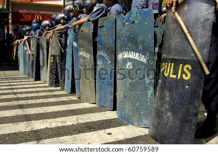 MANILA - MAY 1: Riot policemen get ready to protect Malacanang Palace, the residence of the president, from marching Labor Day protesters in the city of Manila on May 1, 2006. - stock photo