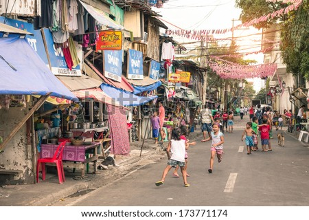 MANILA, PHILIPPINES - 29 JANUARY, 2014: children playing on the street in the district of Intramuros, which was the seat of the government when the Philippines were a component of the Spanish Empire. - stock photo