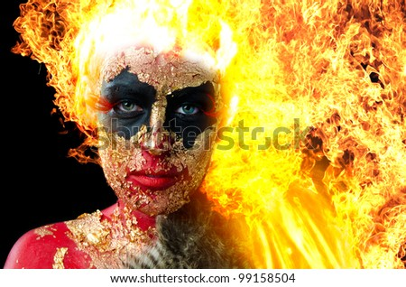 Manipulated image of girl in heavy demon makeup with flames for hair - stock photo