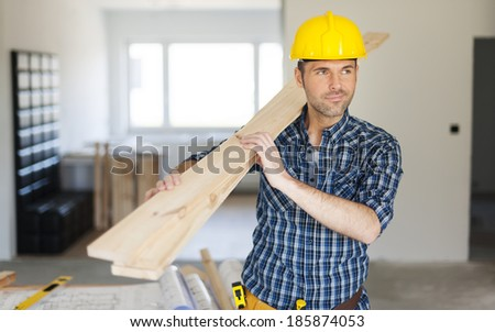Manley construction worker holding wood planks