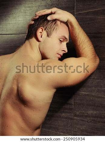 Manly and muscular. Closeup rear view image of sexual man leaning with his hands against the tile wall and looking away with water drops on his skin - stock photo