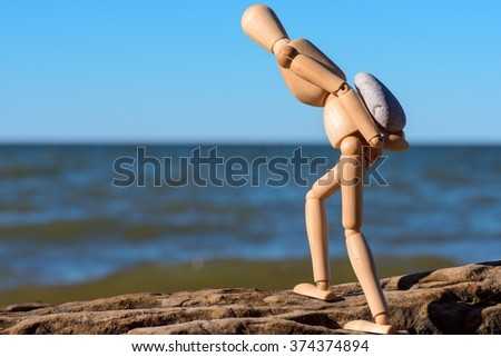 Mannequin carries a heavy stone on the seashore - stock photo