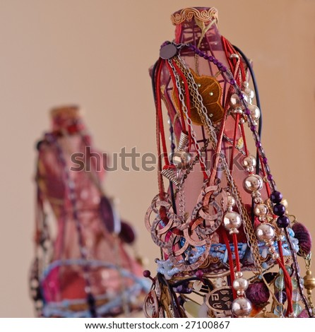 Mannequin covered with necklaces is reflected on a mirror - stock photo
