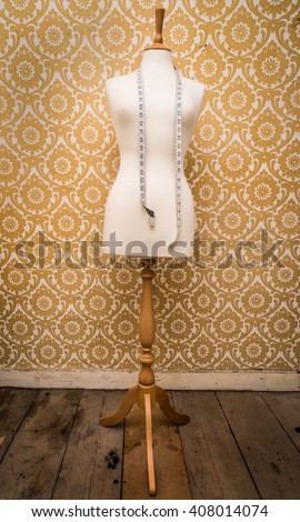mannequin dress form and tape measure vintage  background - stock photo