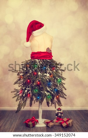 Mannequin dressed for a festive Christmas with pine branches and Santa hat - stock photo