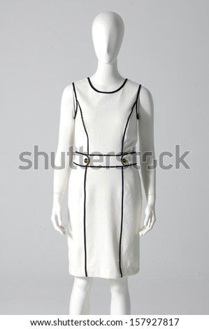 Mannequin dressed in evening gown on gray background