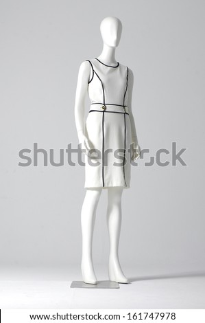 Mannequin dressed in white evening gown on gray background