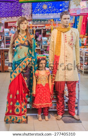 Mannequin family dressed in traditional Indian colorful clothing at the sari street market in Penang, Malaysia - stock photo