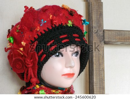 mannequin head girl in the red hat and scarf on the background of the wooden frame