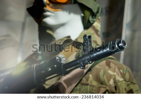 Mannequin in uniform in a military helmet and gun