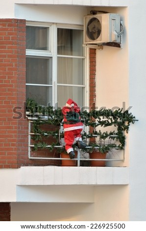 Mannequin Santa Claus climb up onto the balcony of an apartment house