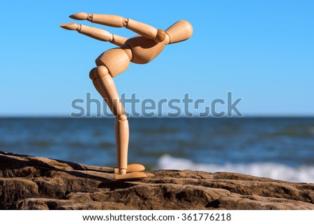 Mannequin stands on the stone and prepares to jump in water - stock photo