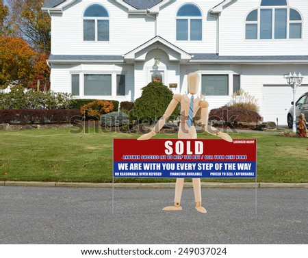 Mannequin wearing blue striped tie holding Real estate sold (another success let us help you buy sell your next home) sign closeup of suburban mcmansion autumn day residential neighborhood USA - stock photo