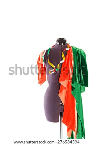 Mannequin with a piece of red and green fabric and measuring tape. The concept of fashion and fashion design. - stock photo
