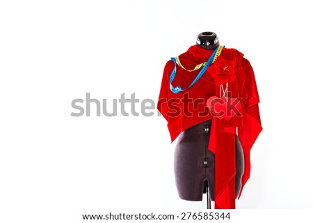 Mannequin with a piece of red cloth and a measuring tape, a flower and a heart from a fabric. The concept of fashion and fashion design. - stock photo