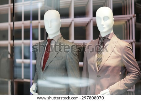 Mannequins behind a storefront glass - stock photo