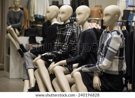 Mannequins in a shop display window - stock photo