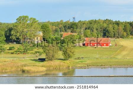 Manor and farm with horses grazing on shore of Baltic Sea - stock photo