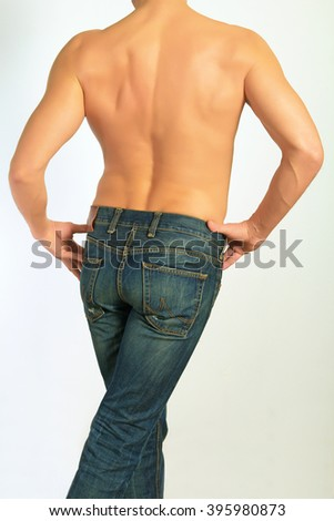 Mans body in jeans back of on a light background.