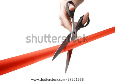 mans hand cutting a red ribbon with scissors - stock photo