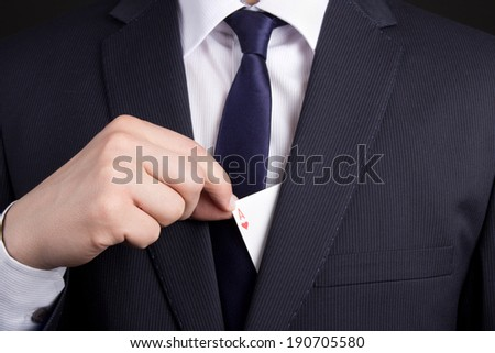 mans hand hiding ace card in business suit pocket