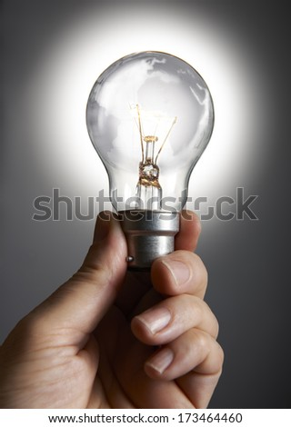 Mans hand holding a light bulb against grey background - stock photo