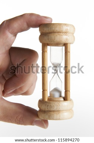 mans hand holding traditional egg timer against white background - stock photo