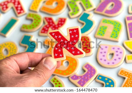Mans hand holds the Hebrew letter Alef ( Aleph)over Hebrew alphabet letters and characters background. - stock photo