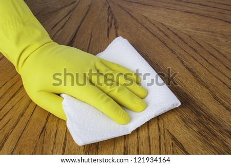 Mans hand in cleaning glove using a paper towel on a wood surface