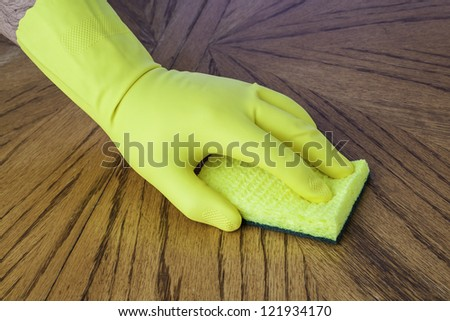 Mans hand in cleaning glove using a sponge on a wood surface - stock photo