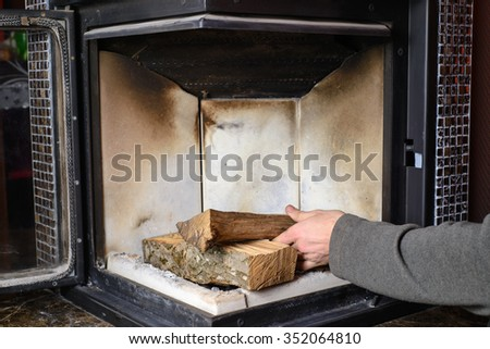 Mans hand load logs in the fireplace - stock photo