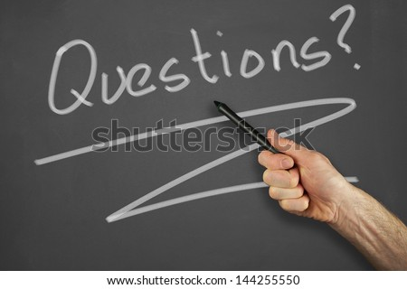 Mans hand pointing to a questions message on a chalkboard.