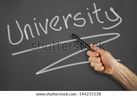 Mans hand pointing to a university message on a chalkboard.