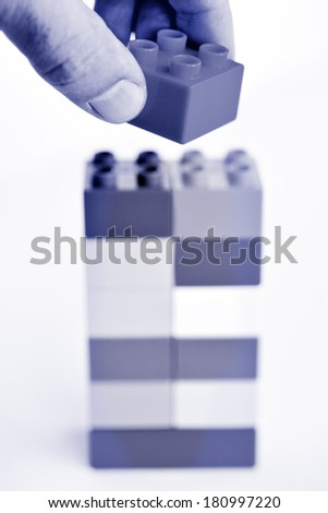 Mans hand puts a toy block on top of a building blocks tower in the background. concept photo of imagination, creativity, planning and ideas (BW) - stock photo