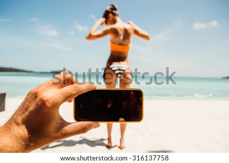 Mans hand taking foto on a the camera on smartphone digital camera of a sporty young beautiful lady in a sexy bikini on a sea shore background. Outdoor lifestyle picture on a hot sunny summer day. - stock photo