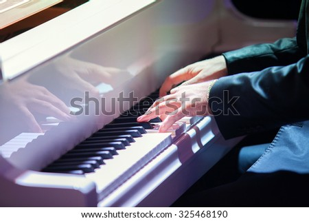 Mans hands playing piano closeup. Selective focus - stock photo