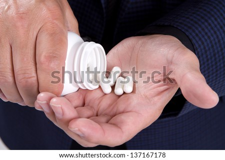 Mans hands shaking out some medicine from a pill bottle. - stock photo