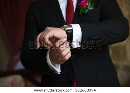 Mans hands with cufflinks. Gentleman in black jacket and white shirt and red tie