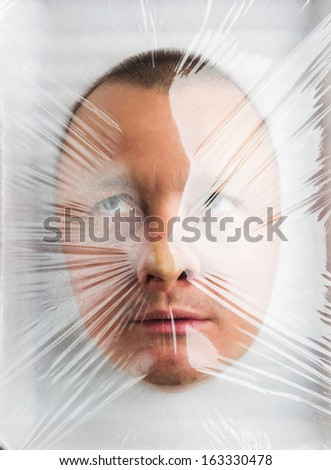 Mans head in Wrapped plastic white food container - stock photo