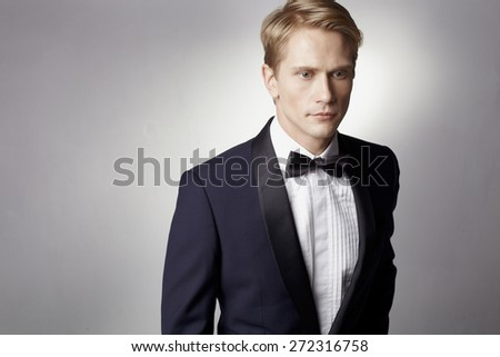 Mans torso in luxury toxedo against gray with light effect - stock photo