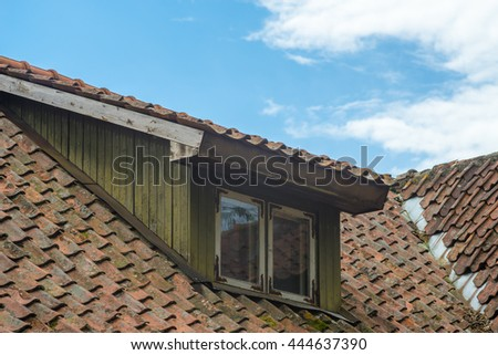 Mansard window in old tiled roof against blue sky - stock photo