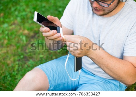 mant connect power bank to his phone to continue listen music