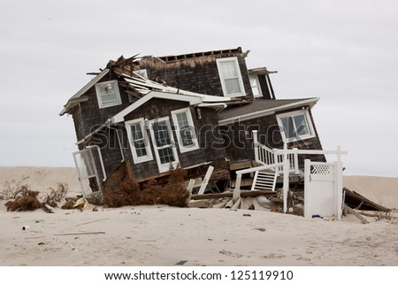MANTOLOKING, NJ - JAN 13: A tilted home off its foundation on the beach on January 13, 2013 in Mantoloking, New Jersey. Clean up continues 75 days after Hurricane Sandy struck in October 2012. - stock photo
