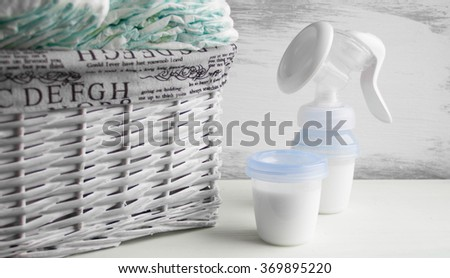 manual breast pump, baby bottle with milk. Mother care breast milk  healthy food newborn baby. Jar with milk in children's room breast feeding, bottle with breastmilk, diapers gray wooden background   - stock photo